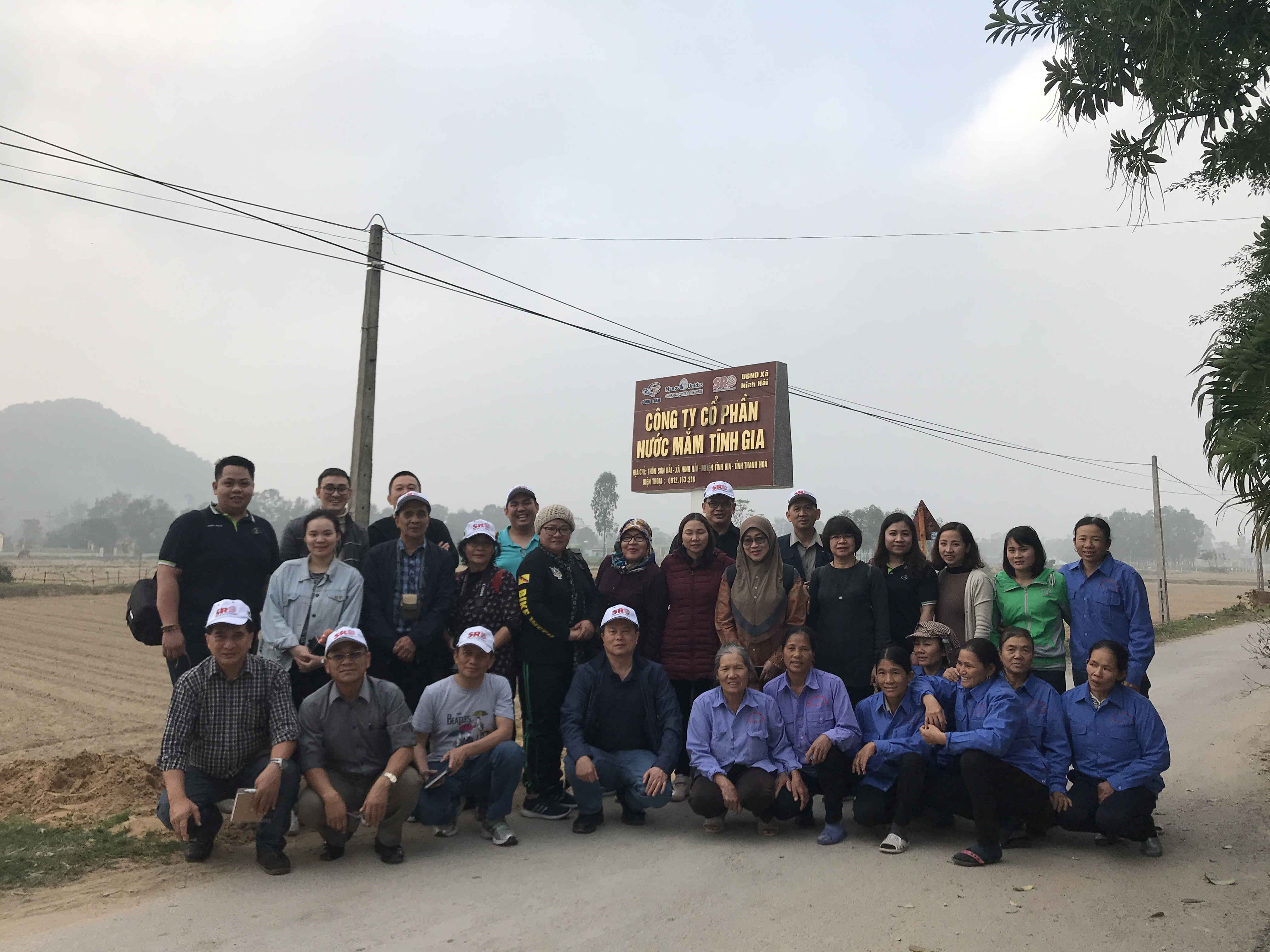 "Taking a group photo with the members of SRD, the founder of the Tinh Gia Fish Sauce Factory JSC, and the women of the Ninh Hai commune who work at the factory The project under SRD and Tinh Gia Fish Sauce Factory provides work oppurtinities for low-income ""single women-headed households""."