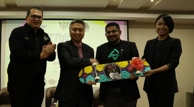 Datuk Snowdan Lawan receiving a souvenir from AZAM and AZAM Young Souls after officiating the launching of the first day of Kuching Youth Day Out (KYDO).